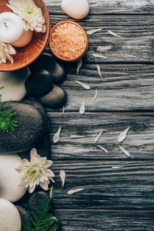 Photo pour Lay plat avec arrangement de traitement spa et massage aux galets, fleurs de sel et de chrysanthème sur fond en bois - image libre de droit