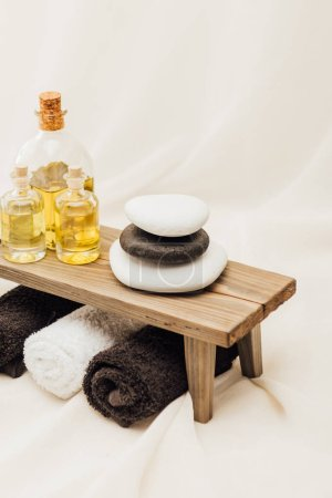 close up view of arrangement of spa treatment accessories with towels, oil and pebbles on white background