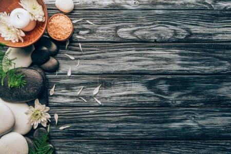 Photo pour Pose plate avec spa et massage arrangement de traitement avec des cailloux, du sel et des fleurs de chrysanthème sur table en bois - image libre de droit