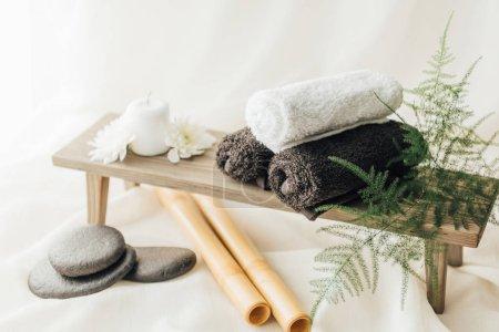 Photo pour Bouchent la vue de disposition des accessoires de traitement spa avec serviettes et cailloux sur fond blanc - image libre de droit