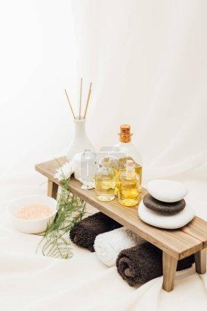 Photo pour Vue rapprochée de l'agencement des accessoires de soins spa avec serviettes, huile et sel sur fond blanc - image libre de droit