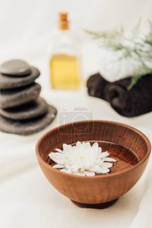 selective focus of arrangement of spa treatment accessories and chrysanthemum flower in wooden bowl on white background