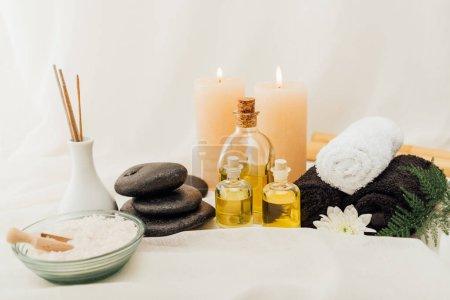 Photo pour Vue rapprochée de l'agencement des accessoires de soins spa avec serviettes, cailloux et huile essentielle sur fond blanc - image libre de droit