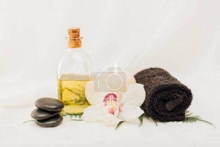 Photo pour Bouchent la vue de disposition des accessoires de traitement spa avec huile, serviette et fleur d'orchidée sur fond blanc - image libre de droit