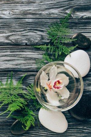 Photo pour Plat Posez avec spa et massage arrangement de traitement avec la fleur de fougère, de cailloux et d'orchidée dans un bol sur la table en bois - image libre de droit