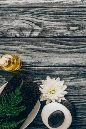 Photo pour Plat Posez avec spa et massage arrangement de traitement avec l'huile, serviette, cailloux et chrysanthème fleur sur le dessus de table en bois - image libre de droit