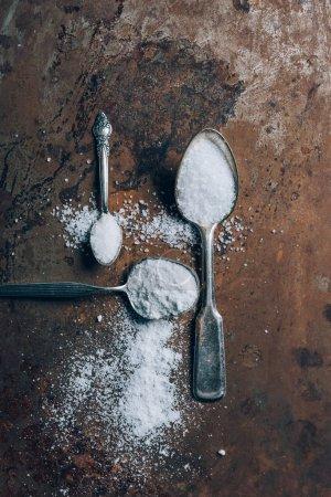 Foto de Vista superior de tres cucharas de plata con la sal de mesa - Imagen libre de derechos