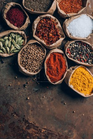 top view of colorful spices in paper bags on table