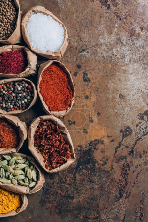 elevated view of colorful spices in paper bags on table