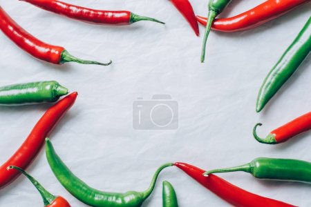 Photo for Top view of red and green chili peppers on white tabletop - Royalty Free Image
