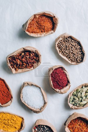 Photo for Top view of colorful indian spices in paper bags on white table - Royalty Free Image