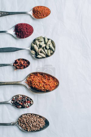 top view of colorful spices in spoons on white table