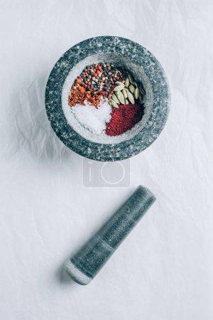 Photo pour Vue de mortier avec épices et pilon sur tableau blanc - image libre de droit
