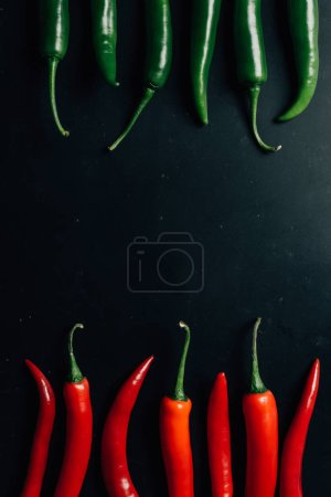 top view of red and green chili peppers on dark table