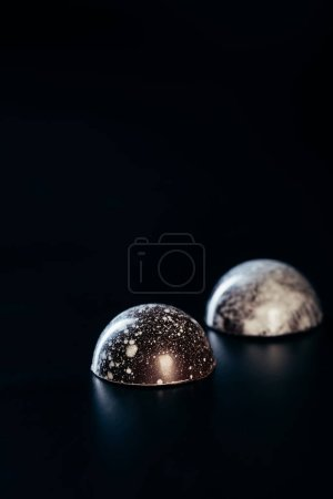 close up view of two chocolate candies on black background