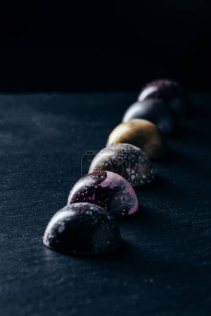 chocolate candies placed in row on black background