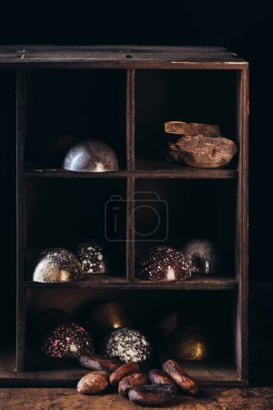 closeup view of nuts, chocolate pieces and candies on shelves on black background