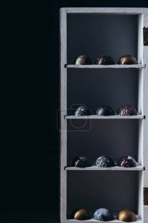 various chocolate candies placed in rows on shelves on black background