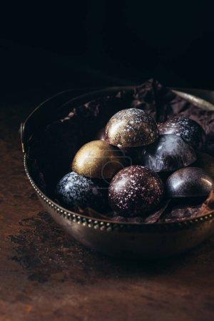 various chocolate candies in metal basket on black background