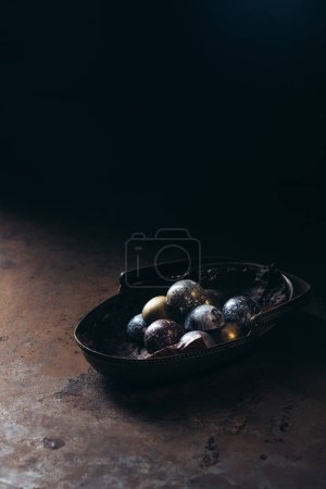 pile of different chocolate candies in metal basket on black background