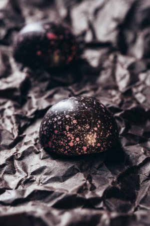 closeup view of two chocolate candies with pink splashes on crumpled paper