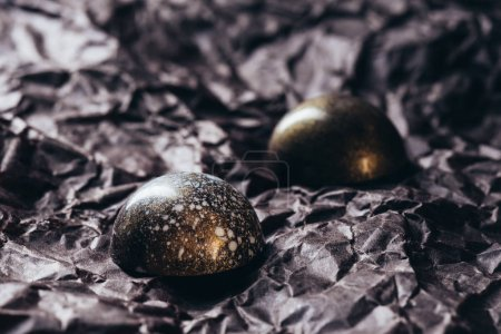 closeup shot of two chocolate candies with golden splashes on crumpled paper