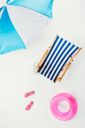 top view of beach umbrella, striped beach chair, flip flops and inflatable ring isolated on white