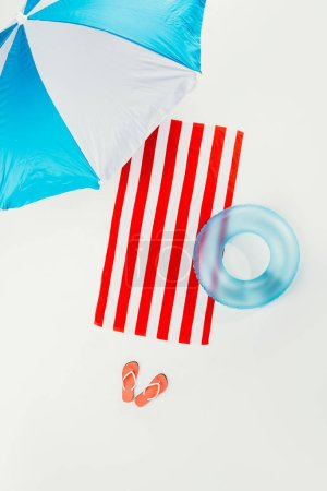 top view of beach umbrella, striped beach towel, flip flops and inflatable ring isolated on white