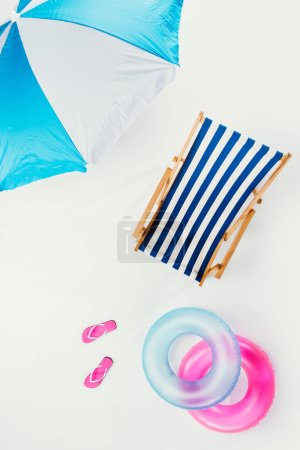 top view of beach umbrella, striped beach chair, flip flops and inflatable rings isolated on white