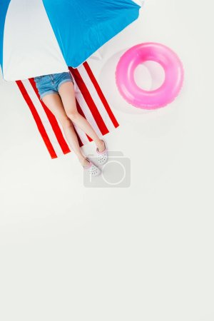 top view of girl lying on striped beach towel under beach umbrella isolated on white