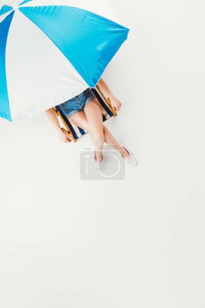 top view of girl sitting on chair under beach umbrella isolated on white