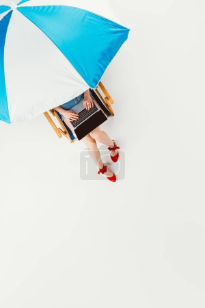 top view of girl sitting in beach chair and using laptop isolated on white