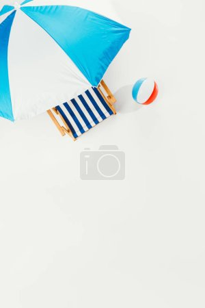 top view of beach umbrella, striped beach chair and inflatable beach ball isolated on white