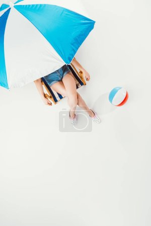 top view of woman sitting on chair under beach umbrella isolated on white