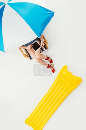 top view of girl using digital tablet while resting on beach chair under umbrella isolated on white