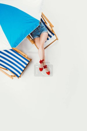 top view of woman resting in chair under beach umbrella isolated on white