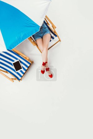 top view of girl resting in chair under beach umbrella isolated on white