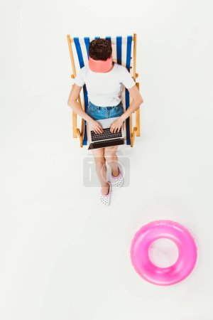 overhead view of woman sitting in striped beach chair and using laptop isolated on white