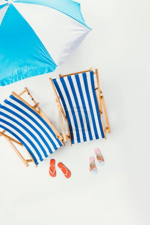 top view of beach umbrella, striped beach chairs and flip flops isolated on white