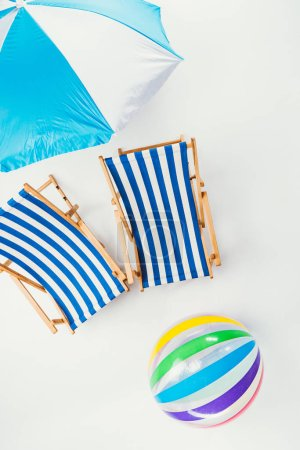 top view of beach umbrella, striped beach chairs and inflatable ball isolated on white