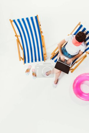 overhead view of woman sitting in beach chair and using laptop isolated on white
