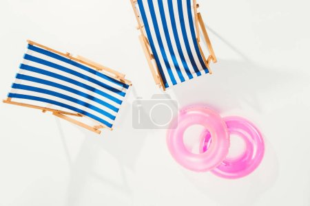 top view of striped beach chairs and inflatable rings isolated on white