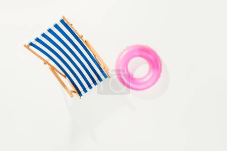 top view of striped beach chair and inflatable ring isolated on white