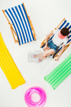 overhead view of girl resting in beach chair between beach items isolated on white
