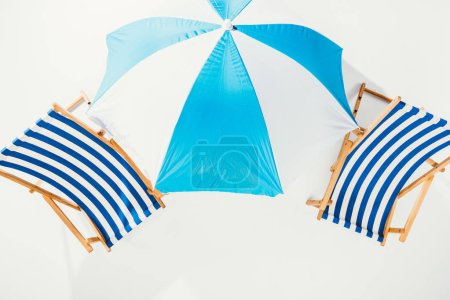 top view of striped beach chairs and beach umbrella isolated on white