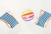 top view of striped beach chairs and inflatable ball isolated on white