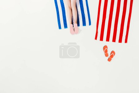 cropped shot of person resting on striped beach towel isolated on white