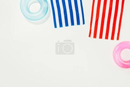 top view of striped towels and inflatable rings isolated on white