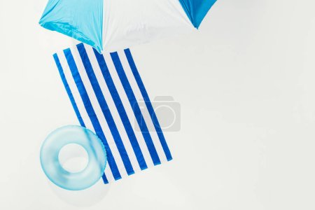top view of beach umbrella, striped towel and inflatable ring isolated on white