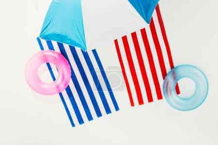 Photo pour Vue de dessus du parasol, serviettes rayées et anneaux gonflables isolés sur blanc - image libre de droit